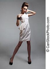 Luxurious female brunette in white dress posing in studio