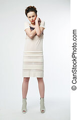 Beauty female in white contemporary dress posing