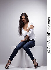 Beauty woman sit in jeans and undress white jacket