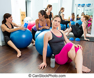 Aerobics pilates women group having a rest at gym talking...