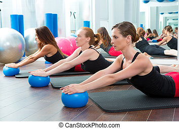 Aerobics pilates women with yoga balls in a row on fitness...