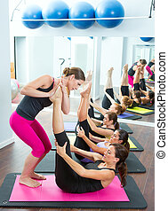 Aerobics Pilates personal trainer helping women group in a...