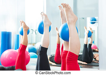 Aerobics pilates women feet with yoga balls in a row on...