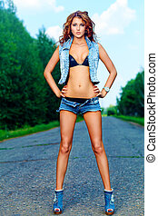hitchhiker - Attractive young woman hitchhiking along a...