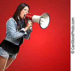portrait of young woman screaming with megaphone against a red background