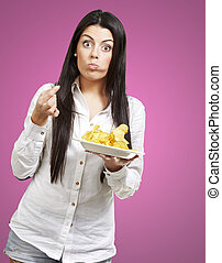 young woman eating potatoe chips against a pink background