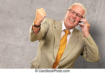 Senior Business Man Using Phone Cheering, Indoor