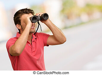 casual man looking into binocular, outdoor