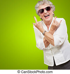 Senior woman wearing sunglasses doing funky action isolated...