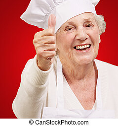 portrait of cook senior woman doing approval gesture over red background