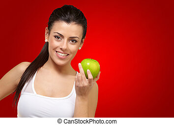 Young woman holding an apple on red background