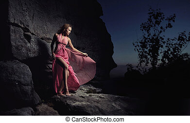 Glamour woman standing next to a rock