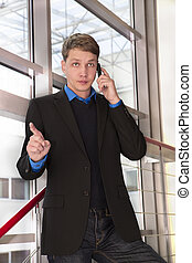 Businessman seriously talking with employees by telephone -...