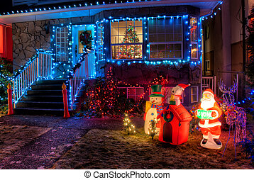 House Decorated with Christmas Lights and ornaments in front...