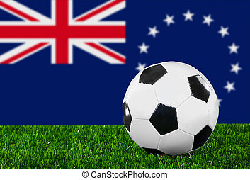 The Cook Islands flag and soccer ball on the green grass.
