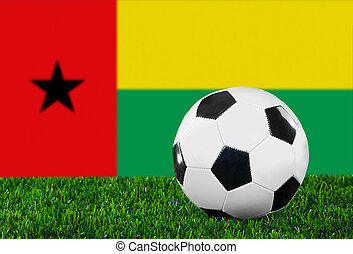 The Guinea-Bissau Flag and soccer ball on the green grass.