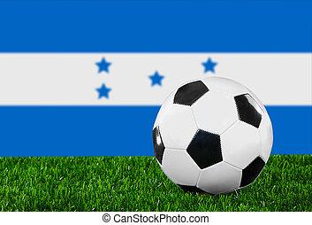The Honduran flag and soccer ball on the green grass.