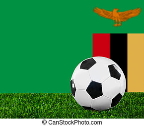 The Zambian flag and soccer ball on the green grass.