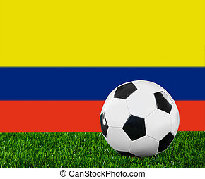 The Colombian flag and soccer ball on the green grass.