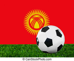 The Kyrgyz Flag and soccer ball on the green grass.