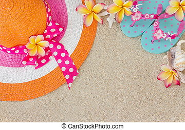 Orange and pink hat and blue Flip Flops in the sand with...