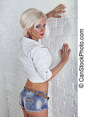 Young sexy girl in white jacket and blue jeans leaning...