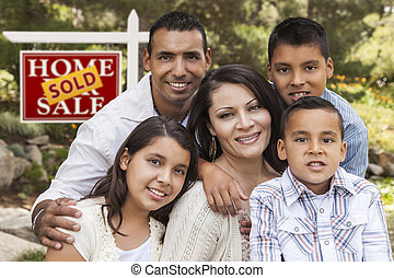 Hispanic Family in Front of Sold Real Estate Sign - Happy...