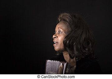 Black Woman Singing - A black woman with bible in hand...