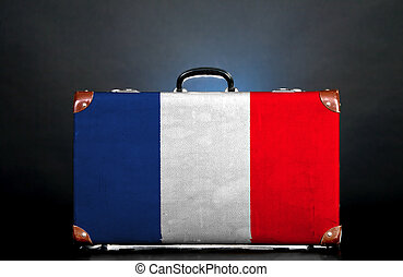 The French flag on a suitcase for travel.
