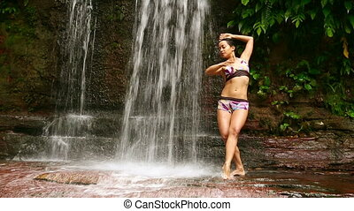 Sexy dancer on waterfall in rainforest