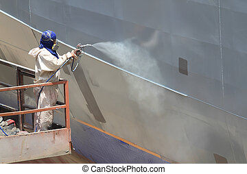 worker painting ship hull using airbrush gray paint