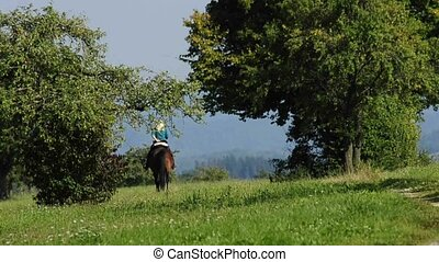 horsewoman riding in the green