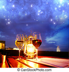 Date under the Sky - A glass of red and white wine besides a...