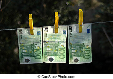 Money laundering - Euro banknotes on a string with clips,...