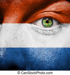 Flag painted on face with green eye to show Netherlands support