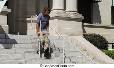 Ankle Brace Crutches - Adult male patient descends steps at...