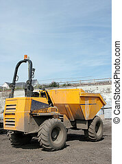 Dumper Truck - Yellow dumper truck standing idle on rough...