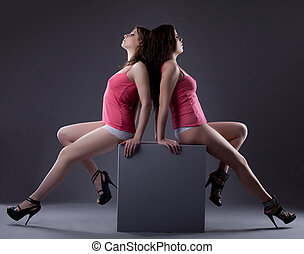 couple of sexy hot women posing on cube