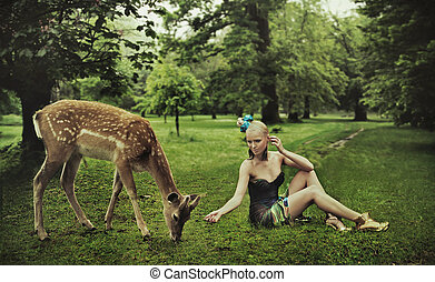 Adorable young lady playing with deer
