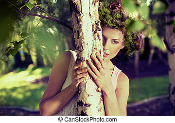 Young attractive woman hiding in forest