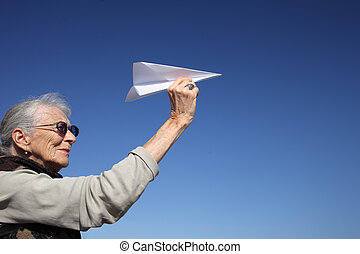 Senior woman with paper plane