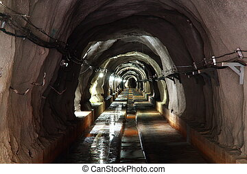 dark tunnel with light - long walk way in dark tunnel with...