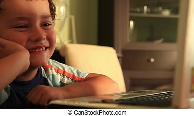 little boy watching notebook and smiling