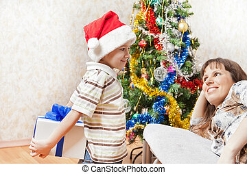 Little son wearing Santa Claus hat giving new year present or christmas holiday gift box to smiling mother