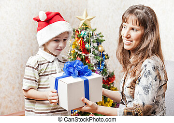 Smiling mother giving new year present or christmas holiday gift box to little son wearing Santa Claus hat
