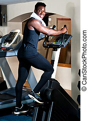 Young smiling fit african male burning calories in the gym...