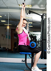 Woman toning her upper and core muscles in multi gym Looking...