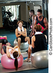 Trainer instructing gym clients on how to use exercise ball