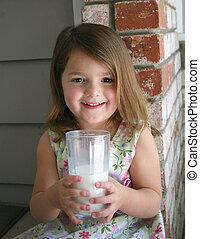 Girl Milk 4 - A very healthy little girl holding a glass of...