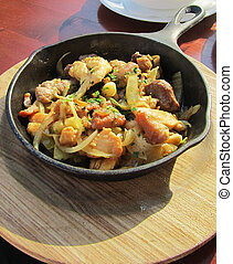 dish of chicken,meat and vegetables - Wooden table with...